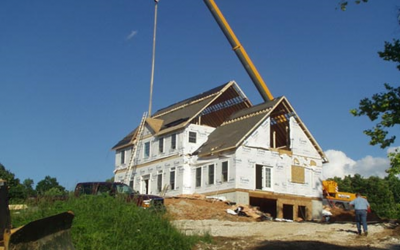 This image shows how huge cranes lift modules of custom modular homes and set them in place to form a home.