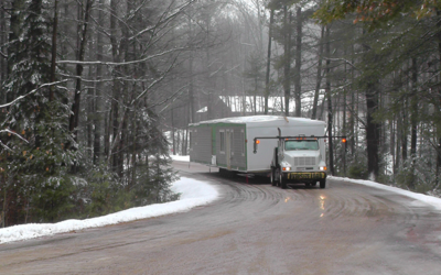 This image shows a custom modular homes module being transported along a highway.